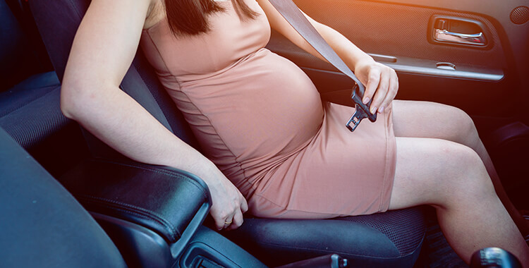 Pregnant Woman Putting on Seat Belt avoiding Car Accident Injuries